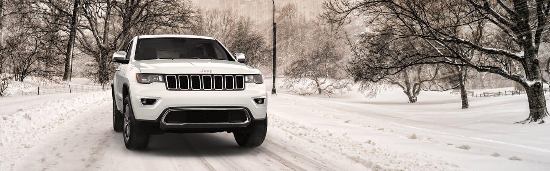 Vista delantera de unJeep Grand Cherokee Limited2021 circulando por una calle cubierta de nieve en la ciudad.