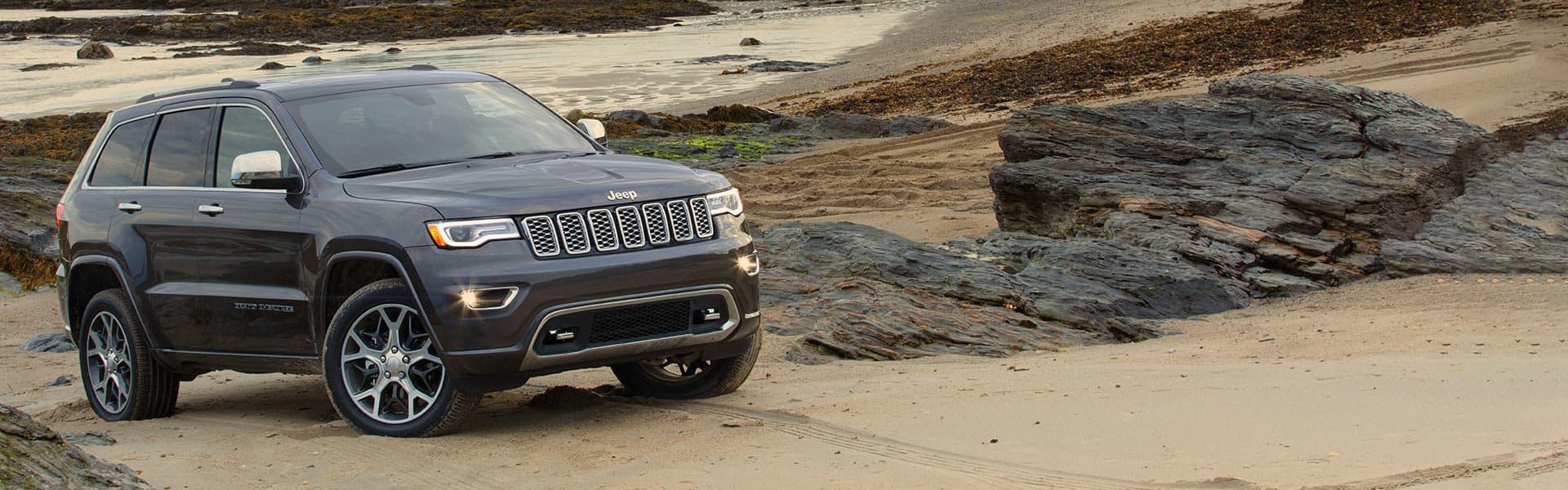Un Jeep Grand Cherokee Overland 2021 gris estacionado sobre un montículo de arena.
