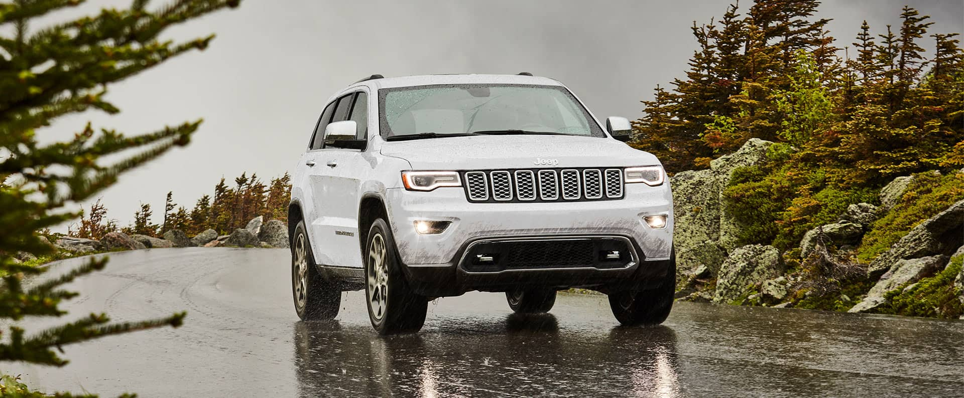 The 2021 Jeep Grand Cherokee Overland being driven on a wet street in the rain.