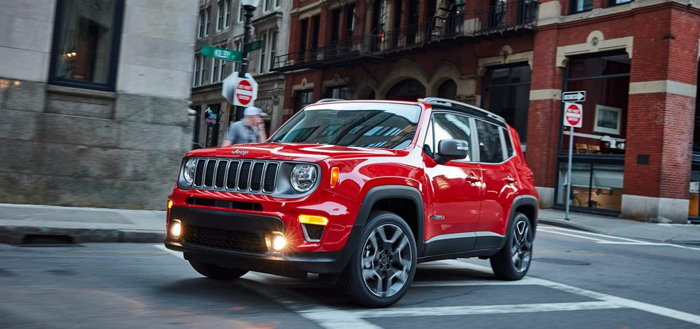 Display A red 2021 Jeep Renegade turning a corner on a busy city street.