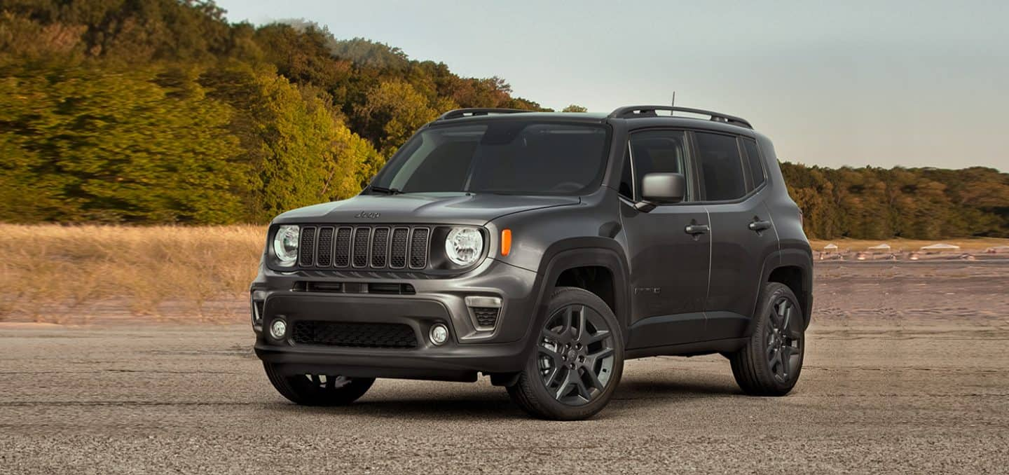 Display A three-quarter front view of a 2021 Jeep Renegade 80th Anniversary Edition parked on sand with trees in the distance.