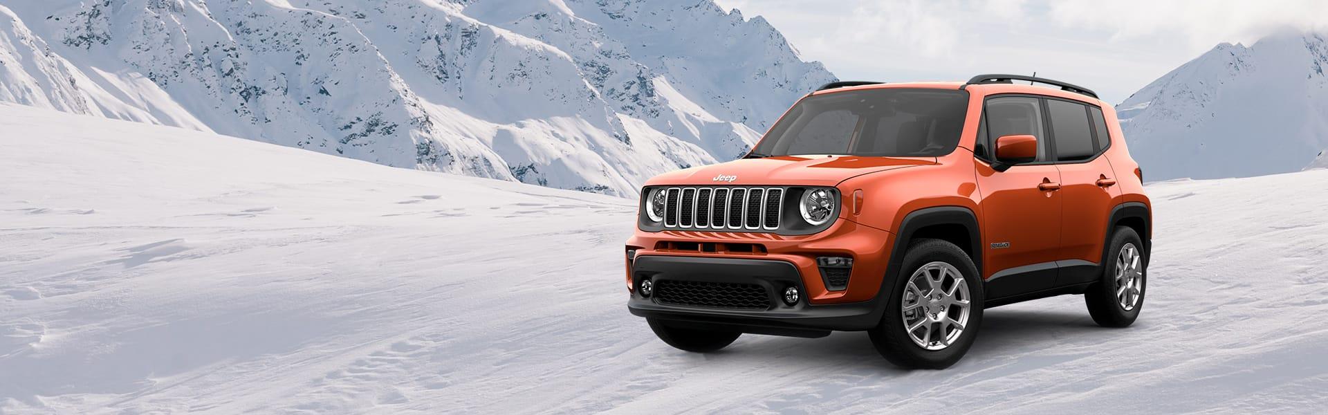Un Renegade Latitude 4x4 2021 sobre un camino cubierto de nieve en las montañas.