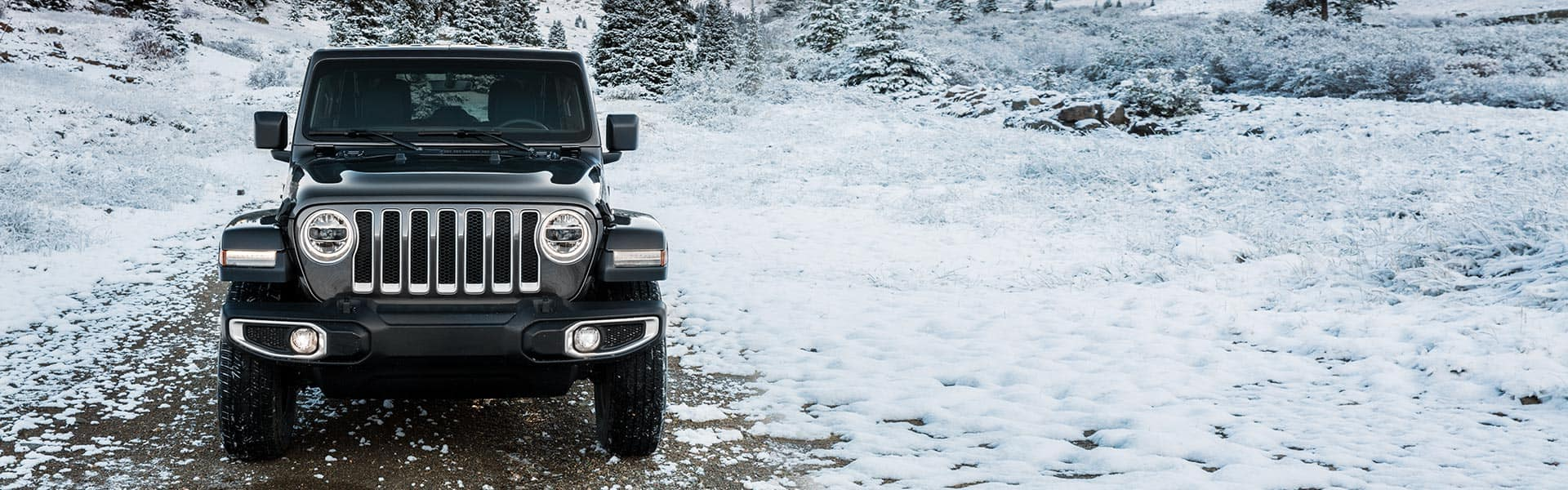 A head-on front view of a 2021 Jeep Wrangler Sahara Unlimited on a snow-covered trail in a wooded area of hills.