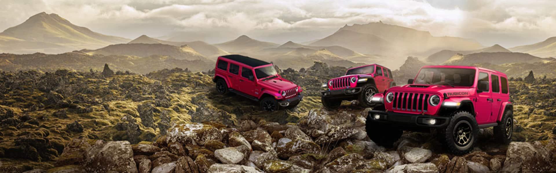 Tres modelos Jeep Wrangler 2021, de izquierda a derecha: un Unlimited Sahara 4xe, un Rubicon 4xe y un Rubicon 392, todos en Tuscadero (un color rosado fuerte), estacionados en una meseta rocosa con montañas con niebla en la distancia.