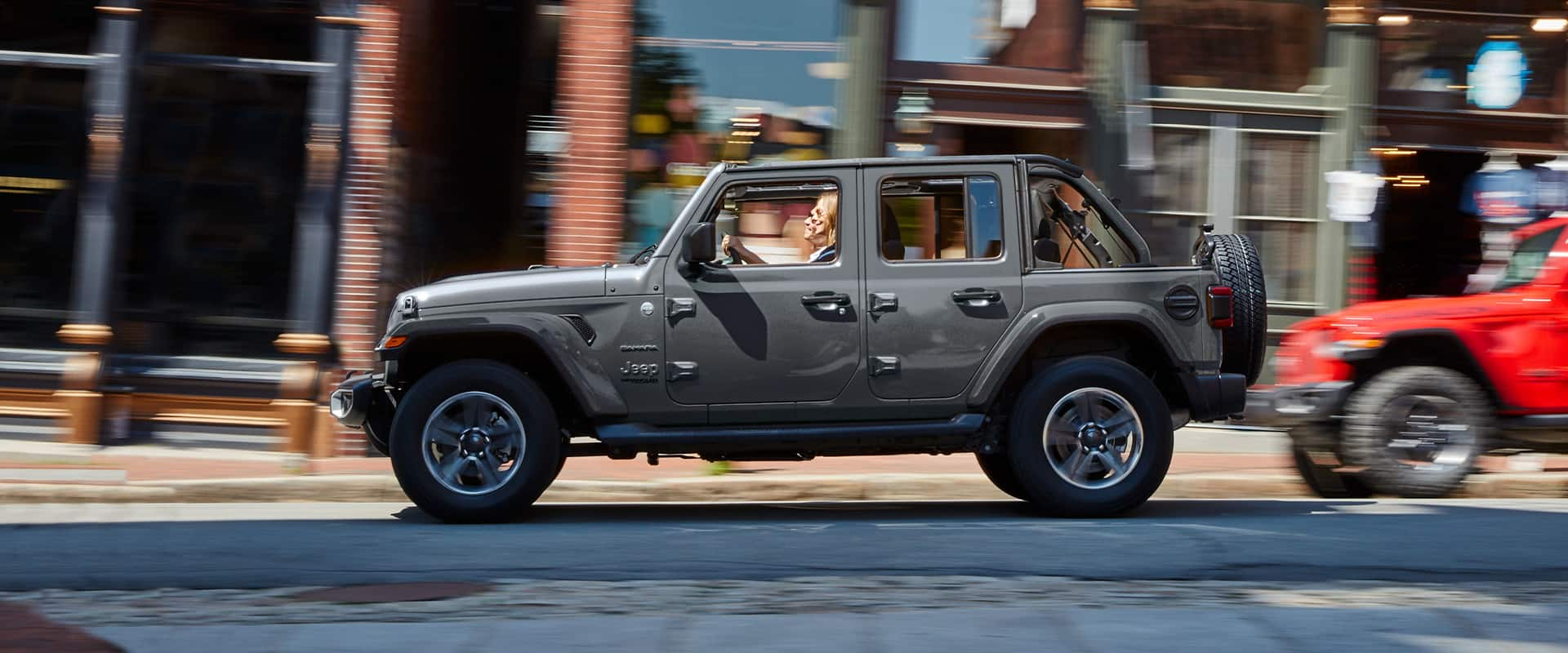 A 2021 Jeep Wrangler Sahara being driven on a busy city street.