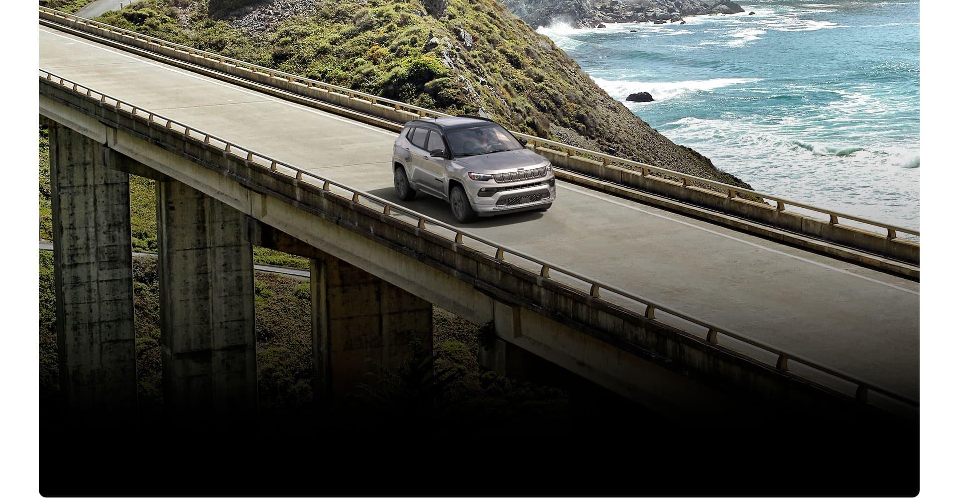 El Jeep Compass High Altitude 2022 circulando por un puente con una montaña que se pierde hacia el mar de fondo.