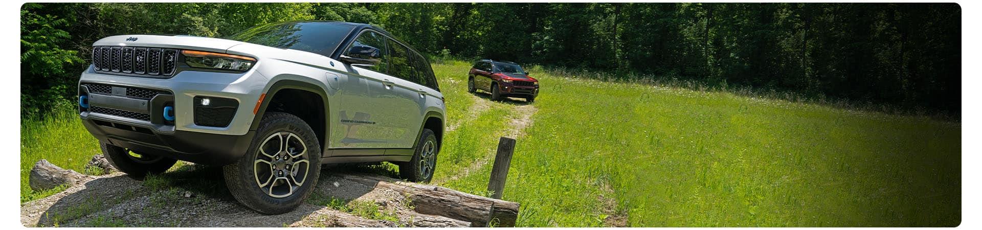 El Jeep Grand Cherokee Trailhawk 4xe 2022 cuesta arriba mientras trepa una pila de troncos.
