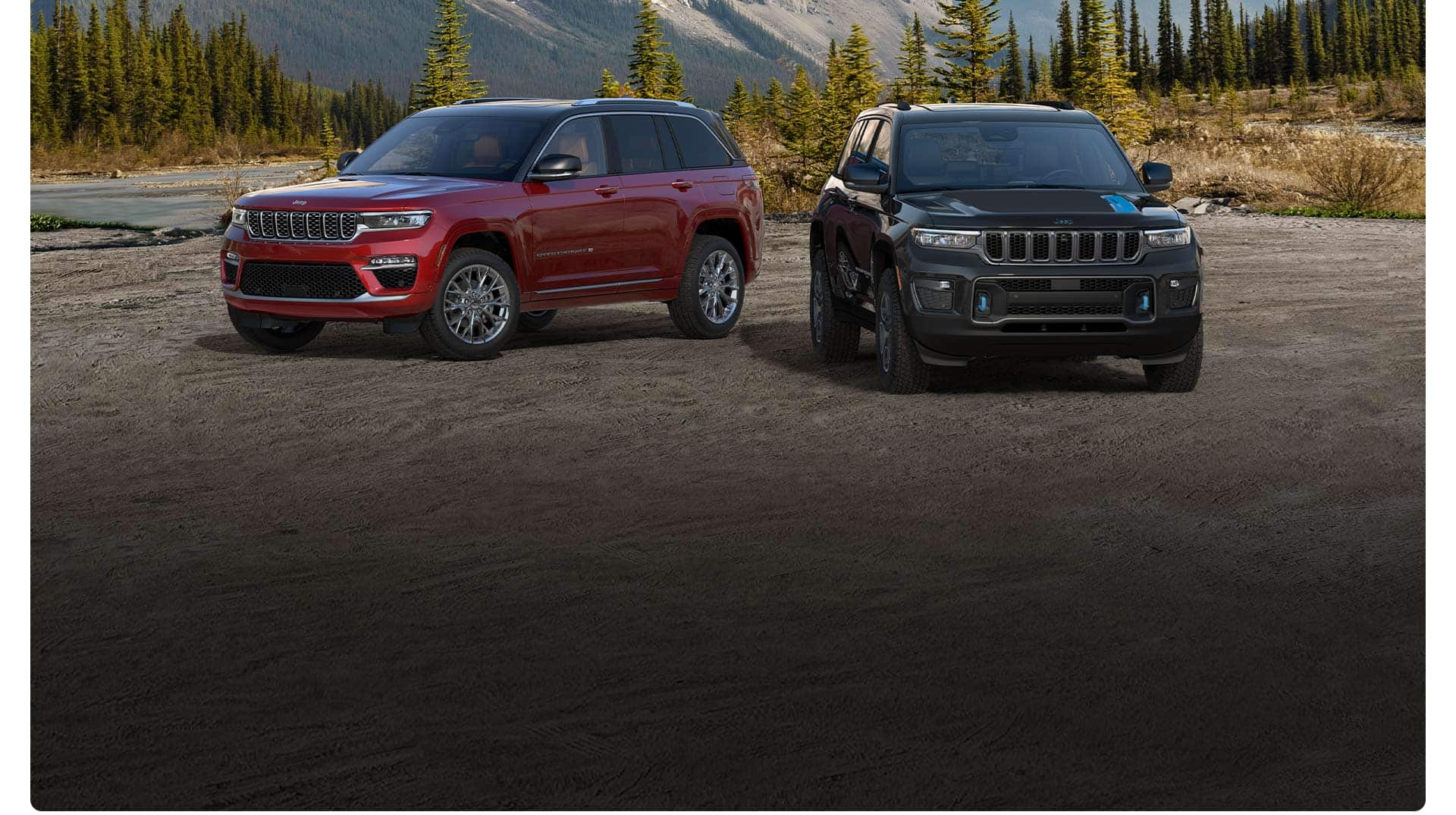 Un Jeep Grand Cherokee Summit y un Grand Cherokee Trailhawk 4xe 2022 estacionados en un valle arenoso con montañas de fondo.