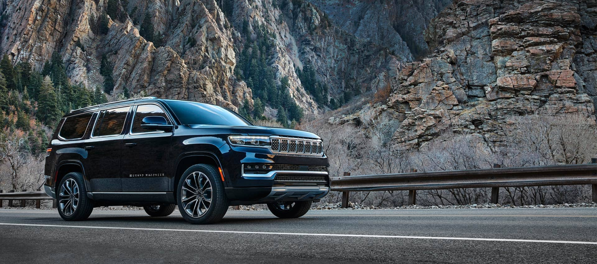 The 2022 Grand Wagoneer parked on the shoulder of a highway against a backdrop of soaring mountains.