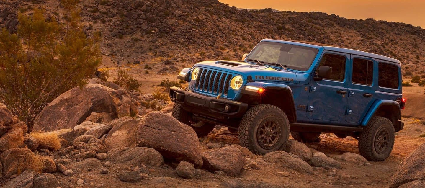 The 2021 Jeep Wrangler Rubicon 392 being driven over rocks in the desert.
