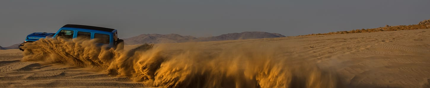 A large dust cloud coming from the wheels of the 2021 Jeep Wrangler Rubicon 392, nearly obscuring the vehicle.