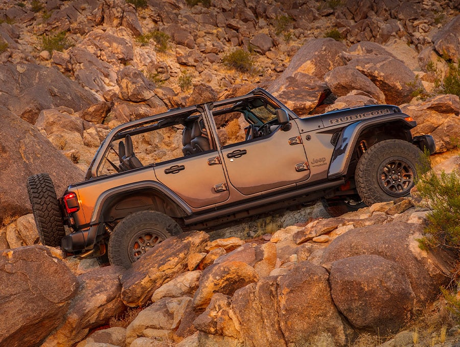 The 2021 Jeep Wrangler Rubicon 392 with half doors, parked facing uphill on a steep, rocky slope.