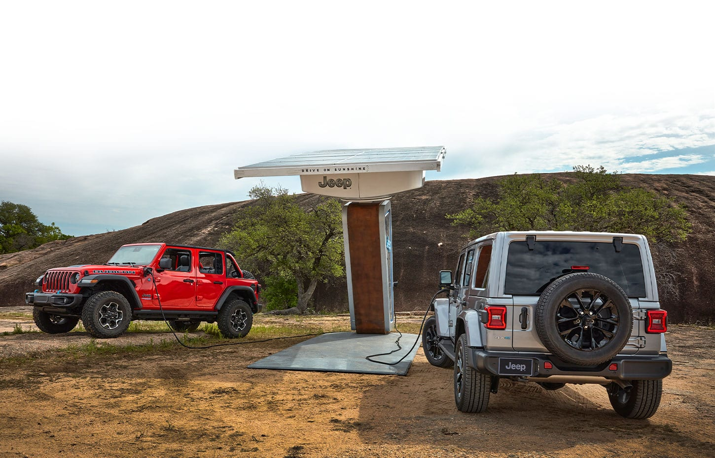A solar-powered Jeep-branded charging station in the desert, bearing the slogan