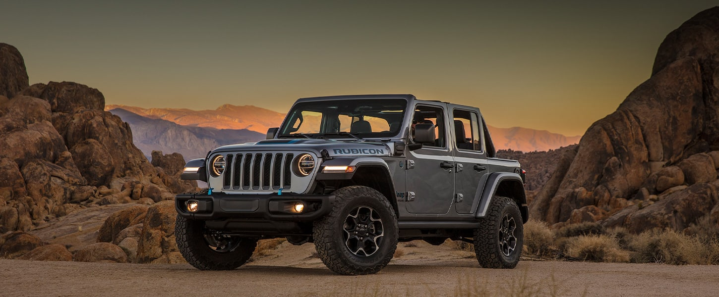 The 2021 Jeep Wrangler 4xe parked in the desert with several rocky outcroppings behind it.