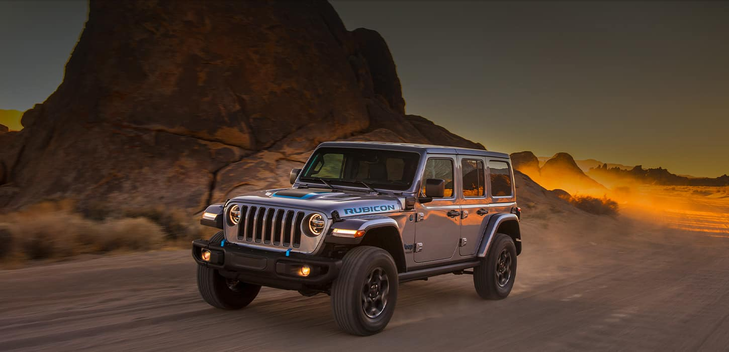 The 2021 Jeep Wrangler 4xe being driven off-road on sandy terrain.