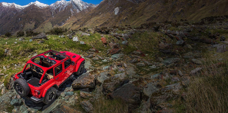 Jeep Wrangler Rubicon andando por un terreno rocoso y montañoso.