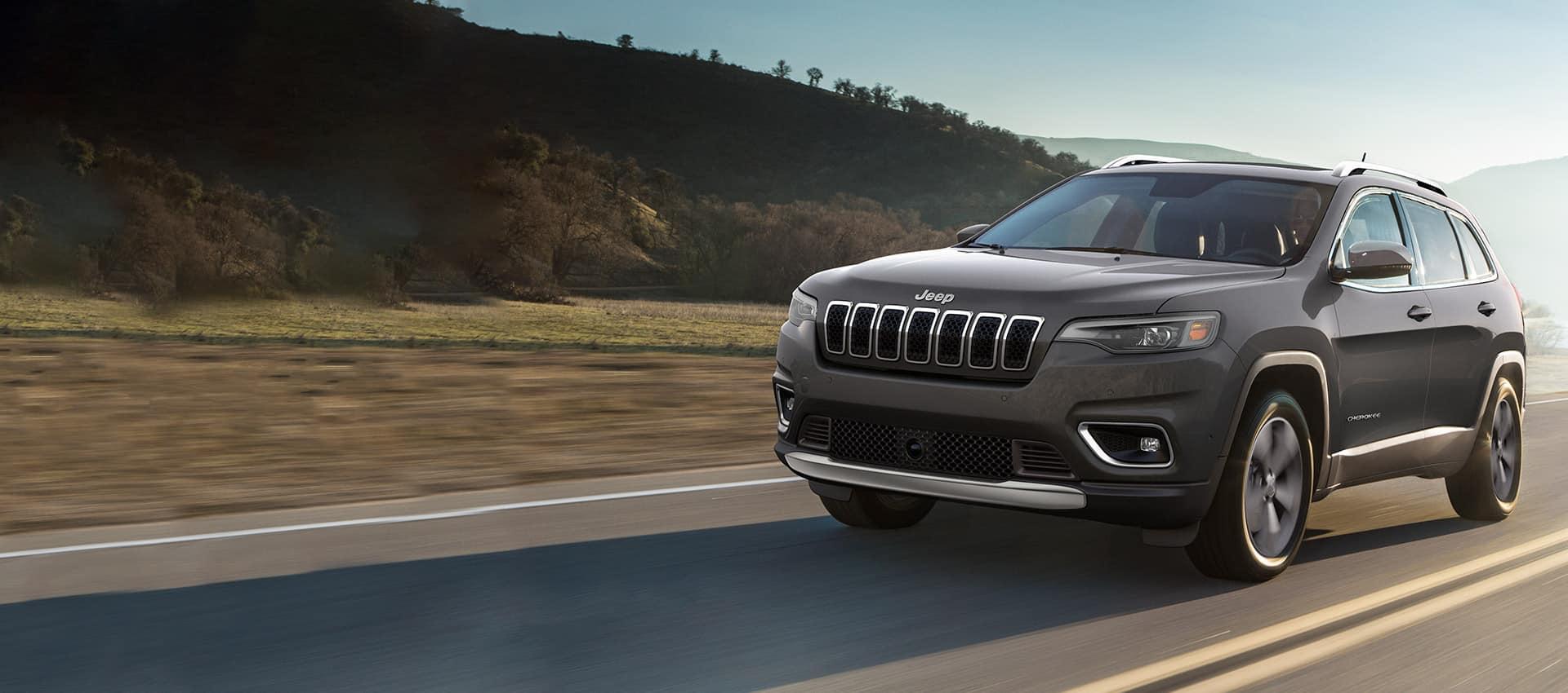 UnJeep Cherokee Limited 2021 andando por una autopista cerca de las montañas.