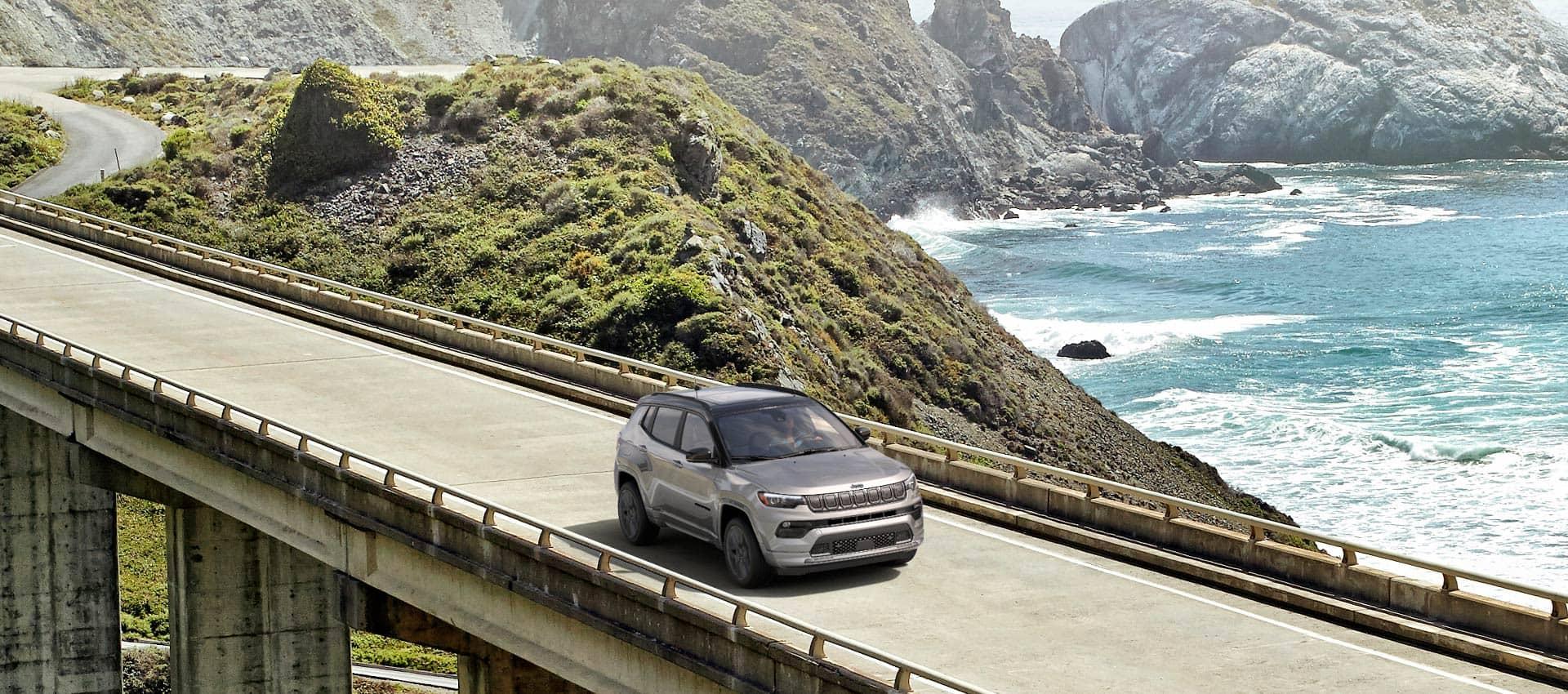 Un Jeep Compass High Altitude 2022 andando por un puente con una montaña que se pierde hacia el mar de fondo.
