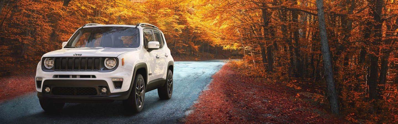 UnJeep® Renegade Limited2020 blanco estacionado en un camino de bosque con luz del sol que se esconde brillando sobre las hojas otoñales de los árboles de fondo.