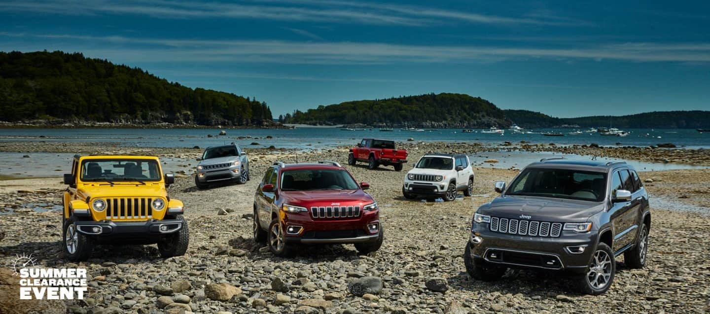 The 2020 Jeep Brand lineup parked on a rocky beach, front row: Wrangler Sahara, Cherokee Limited and Grand Cherokee Overland; back row: Compass Limited, Gladiator Rubicon, Renegade Limited.