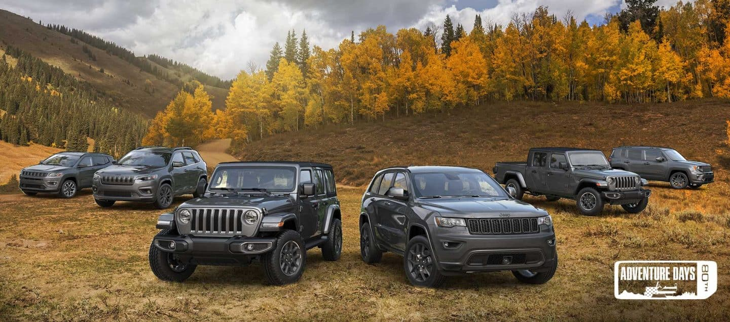 The 2021 80th Anniversary Jeep Brand lineup parked on a grassy autumn terrain , front row: Wrangler 80th Anniversary, Grand Cherokee 80th Anniversary and back row: Compass 80th Anniversary, Cherokee 80th Anniversary, Gladiator 80th Anniversary, Renegade 80th Anniversary. Adventure Day 80th Sales Event Logo.