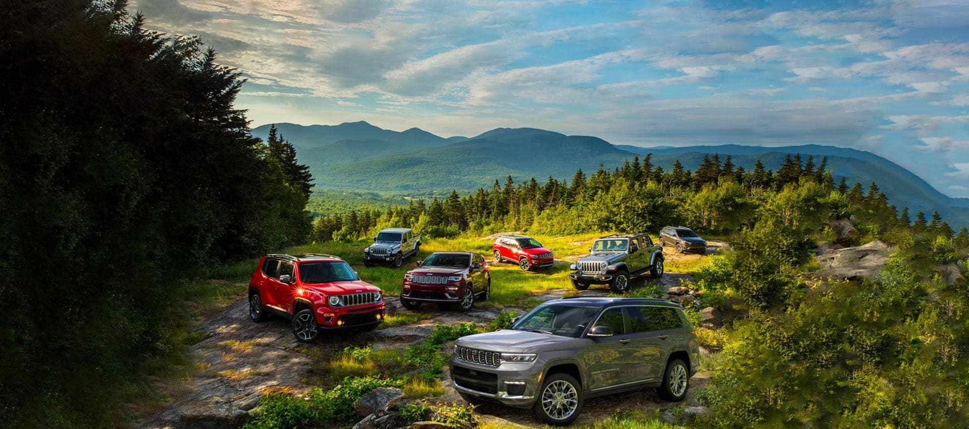 La línea de Jeep2021 estacionada en un claro rocoso en las montañas. En la fila delantera, unJeep Grand Cherokee L, Jeep Renegade Limited, Grand Cherokee Summit y Wrangler Sahara. En la fila trasera, unaJeep Gladiator Overland, Compass Limited y Cherokee High Altitude.