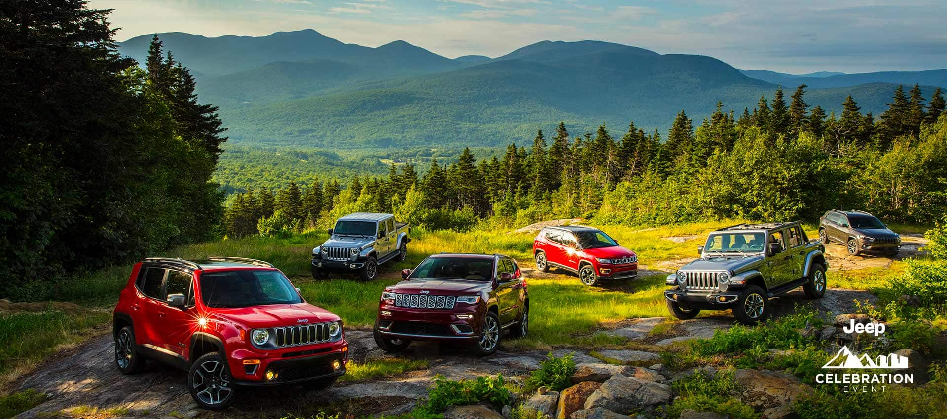 The 2021 Jeep Brand lineup parked on a rocky clearing in the mountains. In the front row, a Jeep Renegade Limited, Grand Cherokee Summit and Wrangler Sahara. In the back row, a Jeep Gladiator Overland, Compass Limited and Cherokee High Altitude. Jeep Celebration Logo.