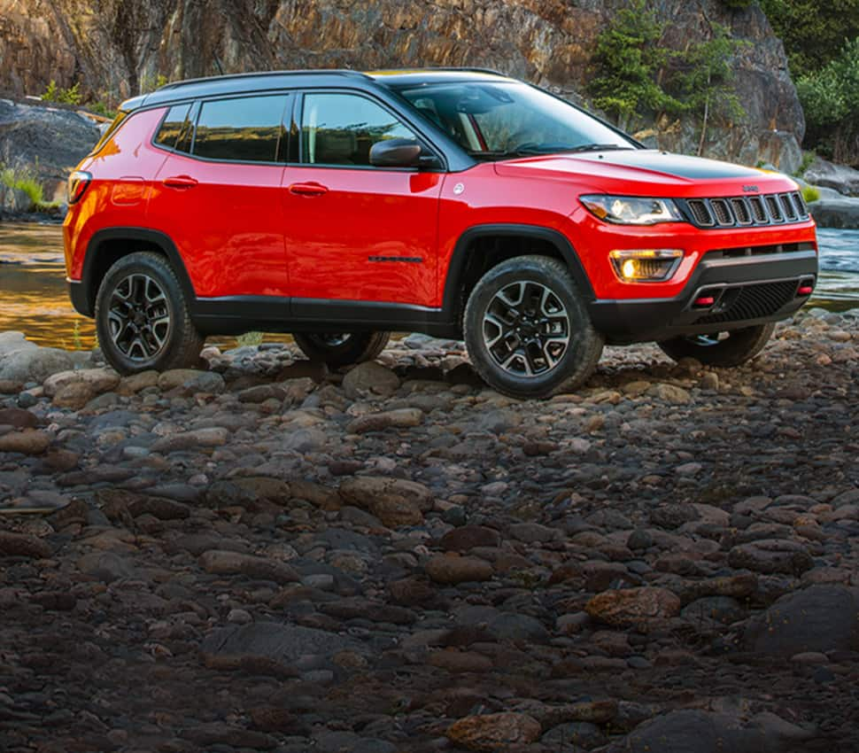 A red 2020 Jeep Compass Trailhawk parked off-road on rocks near a stream.