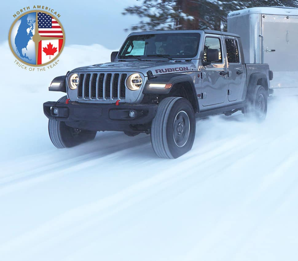 A gray 2020 Jeep Gladiator Rubicon being driven on a snow-covered road, towing a camper.
