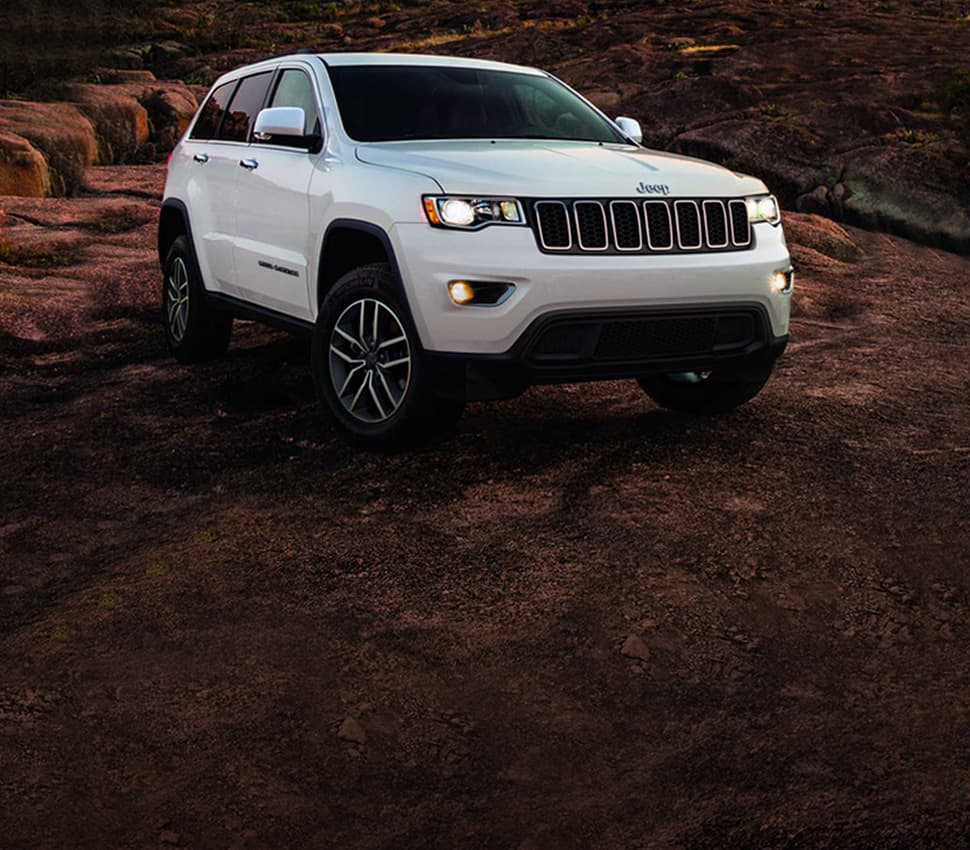 A white 2020 Jeep Grand Cherokee Limited parked off-road in a stony area.
