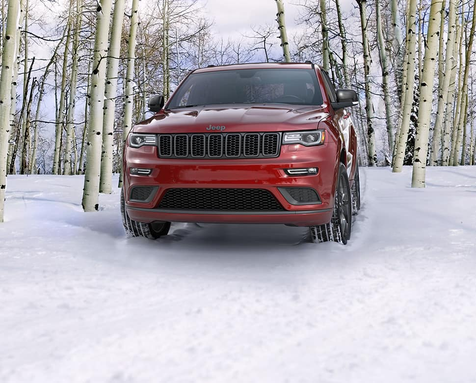 A red 2019 Jeep Grand Cherokee parked in a snow-covered wooded area.
