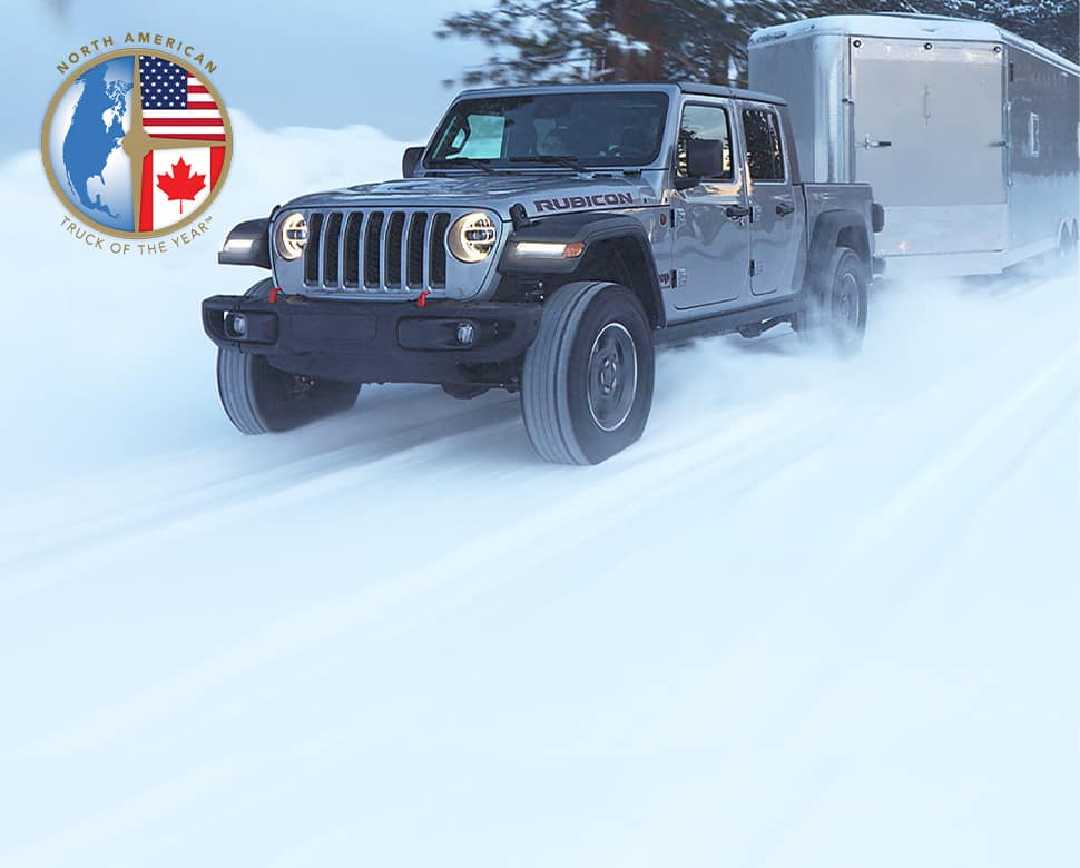 A gray 2020 Jeep Gladiator Rubicon driving on a snow-covered road, towing a camper.