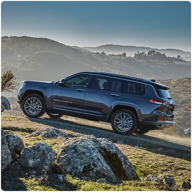 The 2021 Jeep Grand Cherokee L Summit ascending a rocky off-road trail.