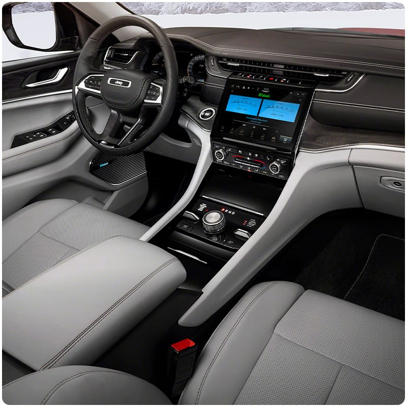 The interior of the 2021 Jeep Grand Cherokee L focusing on the front-row seats and dashboard.