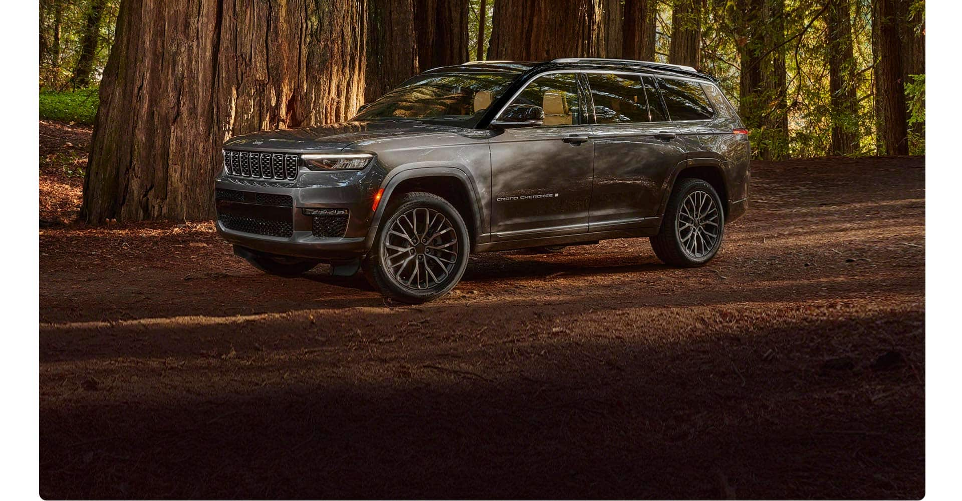 A side profile view of the 2021 Jeep Grand Cherokee L Summit parked on a trail in the forest.