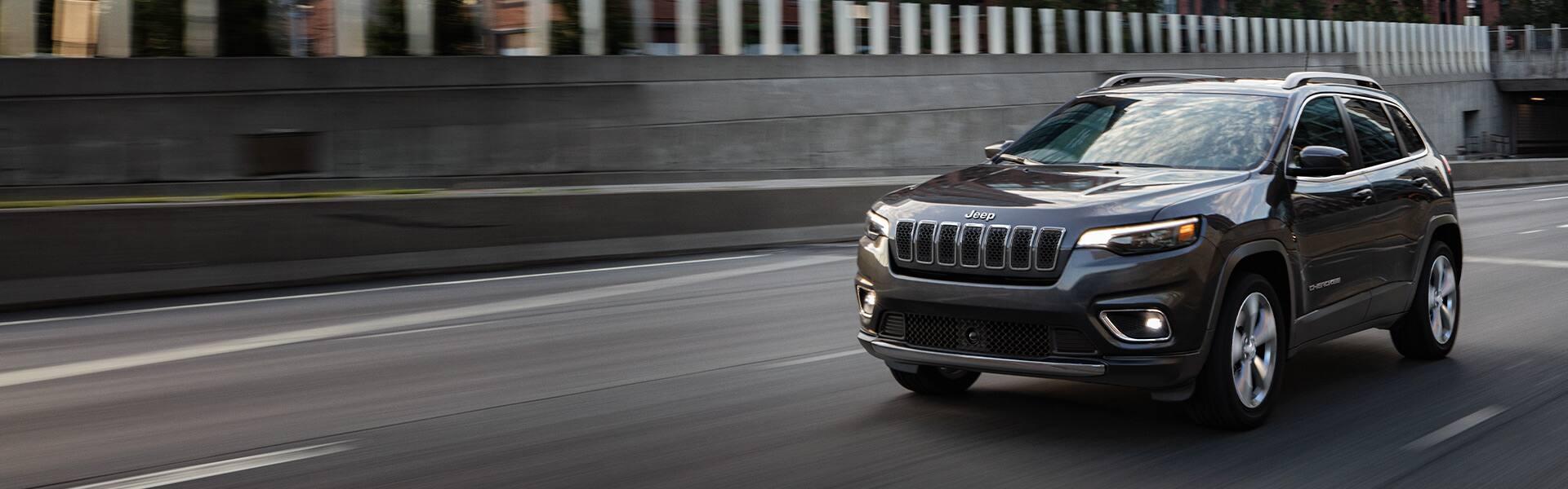 Un Jeep Cherokee Limited 2021 andando por una autopista en una ciudad.
