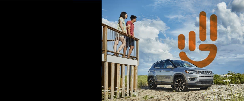 Una pareja parada en una terraza mirando hacia unJeep Compass2021 estacionado con el logoJeep Wave superpuesto en la imagen.