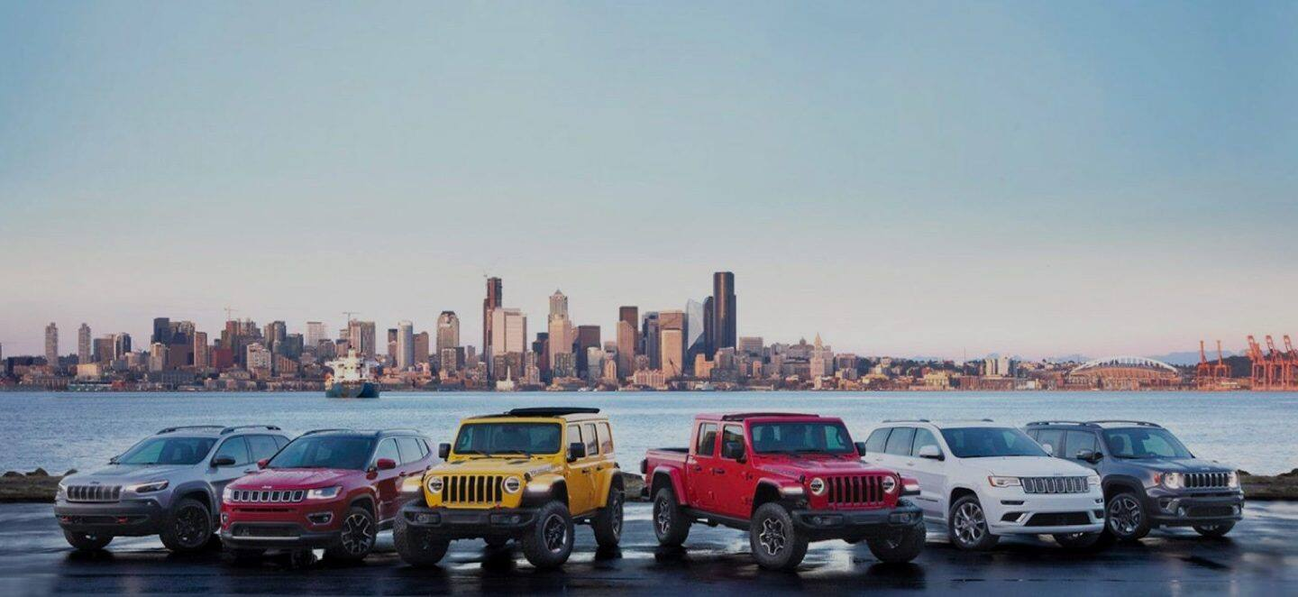 The 2020 Jeep Brand lineup--Cherokee, Compass, Wrangler, Gladiator, Grand Cherokee and Renegade parked at the waterfront.