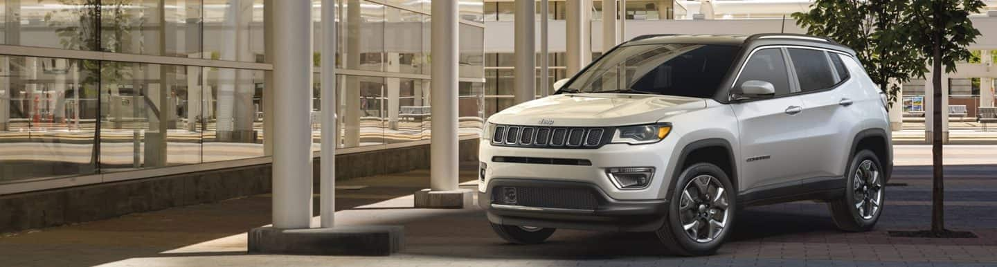 A 2020 Jeep Compass parked on a brick driveway, next to a commercial building.