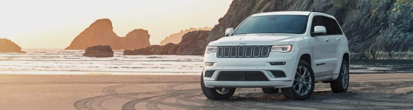 A 2020 Jeep Grand Cherokee parked on sand at a beach.
