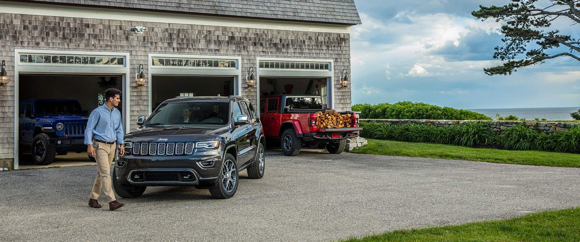A 2020 Jeep Grand Cherokee parked in front of a garage with a 2020 Jeep Wrangler and a 2020 Jeep Gladiator parked inside.