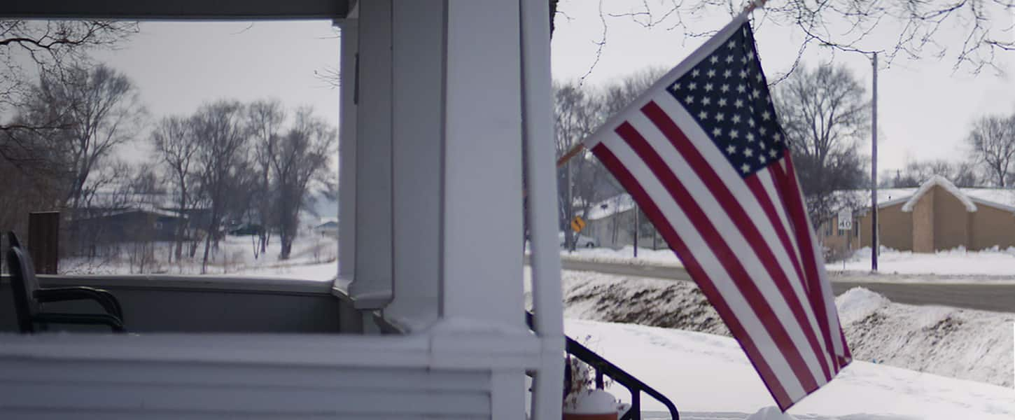 A snow-covered front porch of a home with an American flag waving in the breeze.