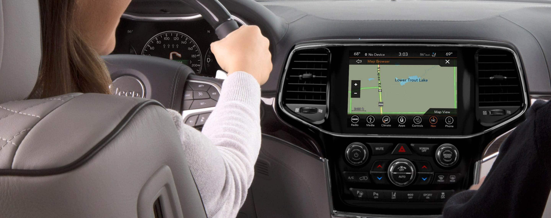 La conductora en un Jeep Grand Cherokee2021 con las manos en el volante, mira la pantalla táctil Uconnect donde se muestra un mapa de ruta.