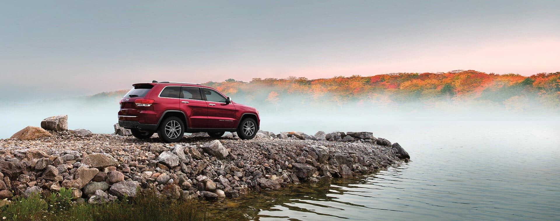 UnJeep Grand Cherokee Limited4x42021 estacionado en un espigón rocoso junto a un lago.