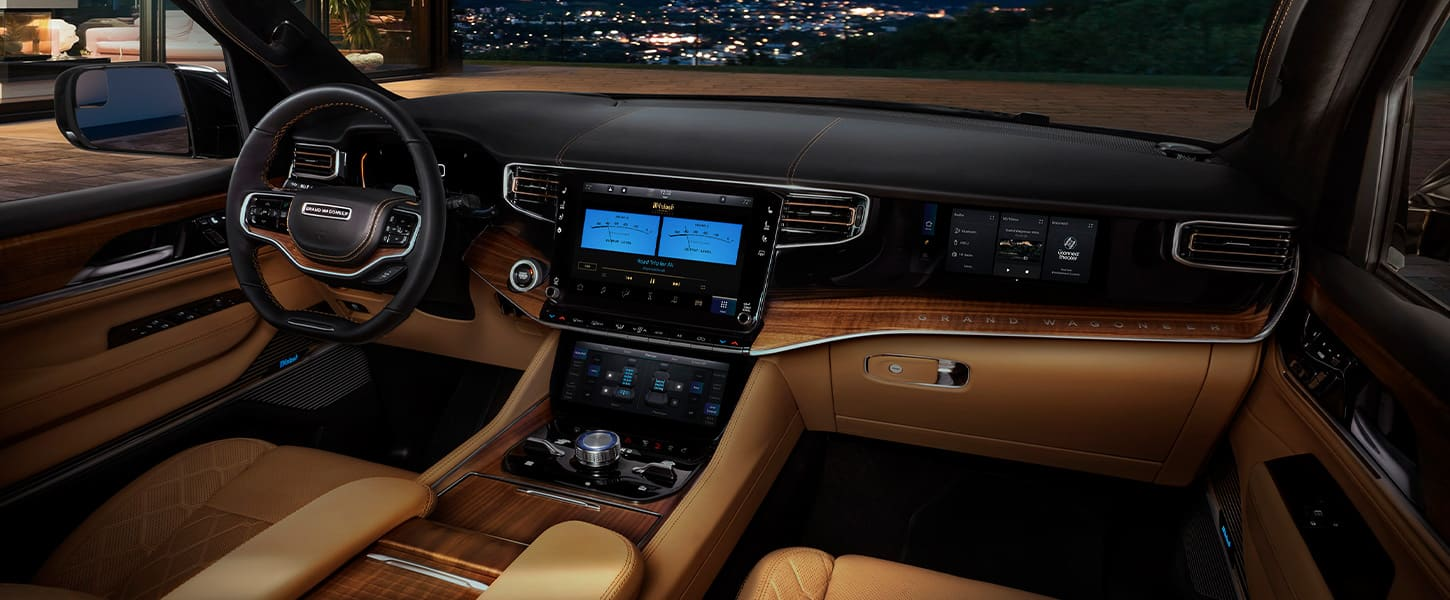 A sweeping view of the instrument panel, dash, steering wheel and touchscreen in the 2022 Wagoneer.